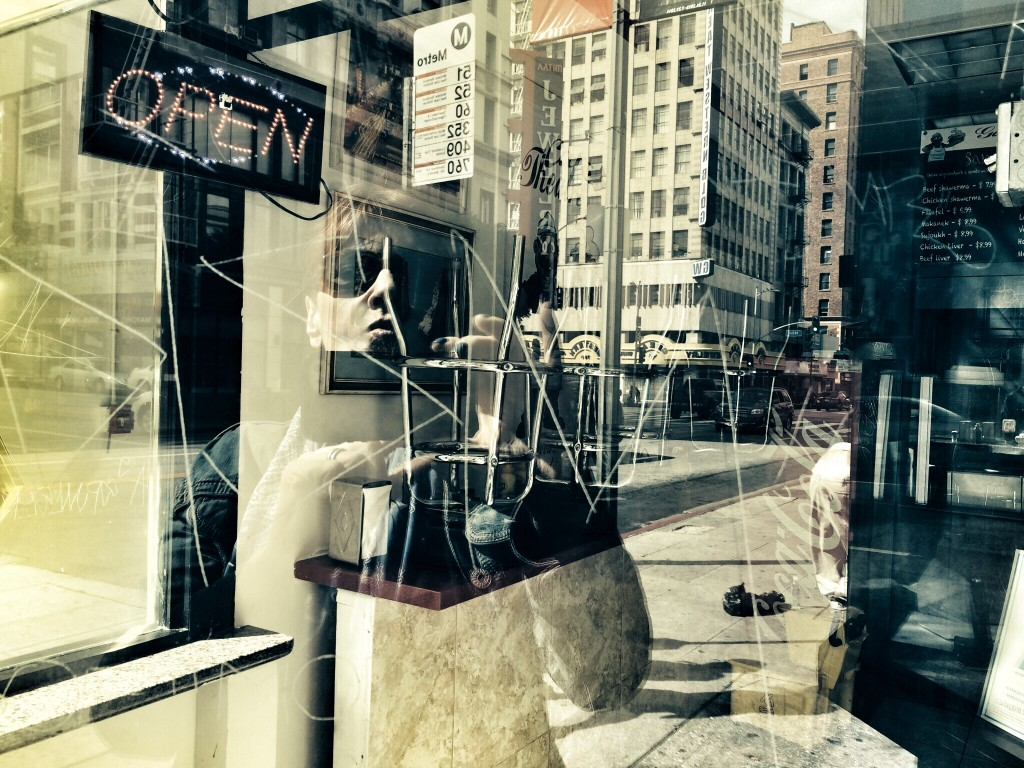 Alexis Rhone Fancher reflected in a Los Angeles window